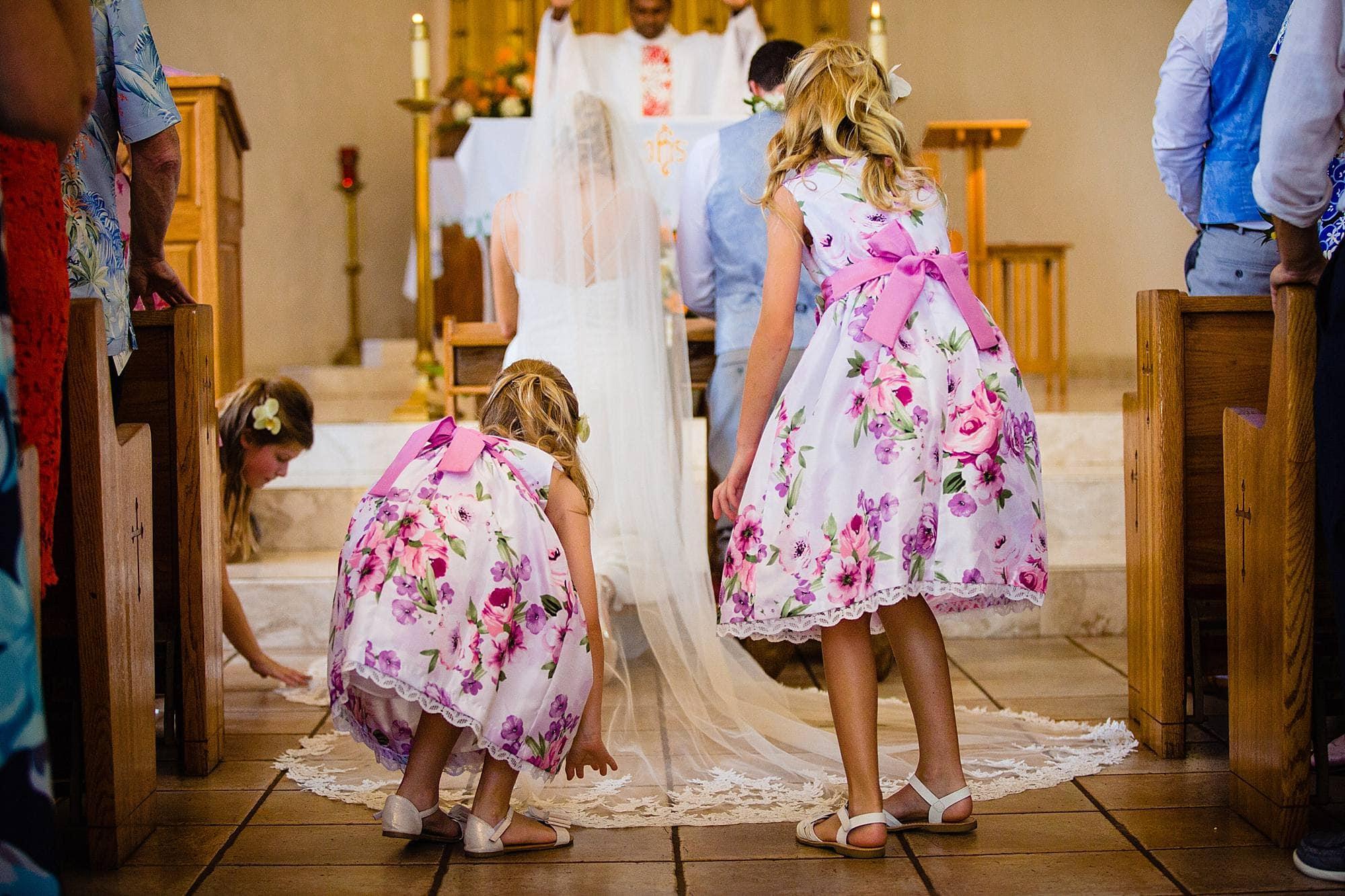 flower girls adjusting veil of bride at maria lanikila church