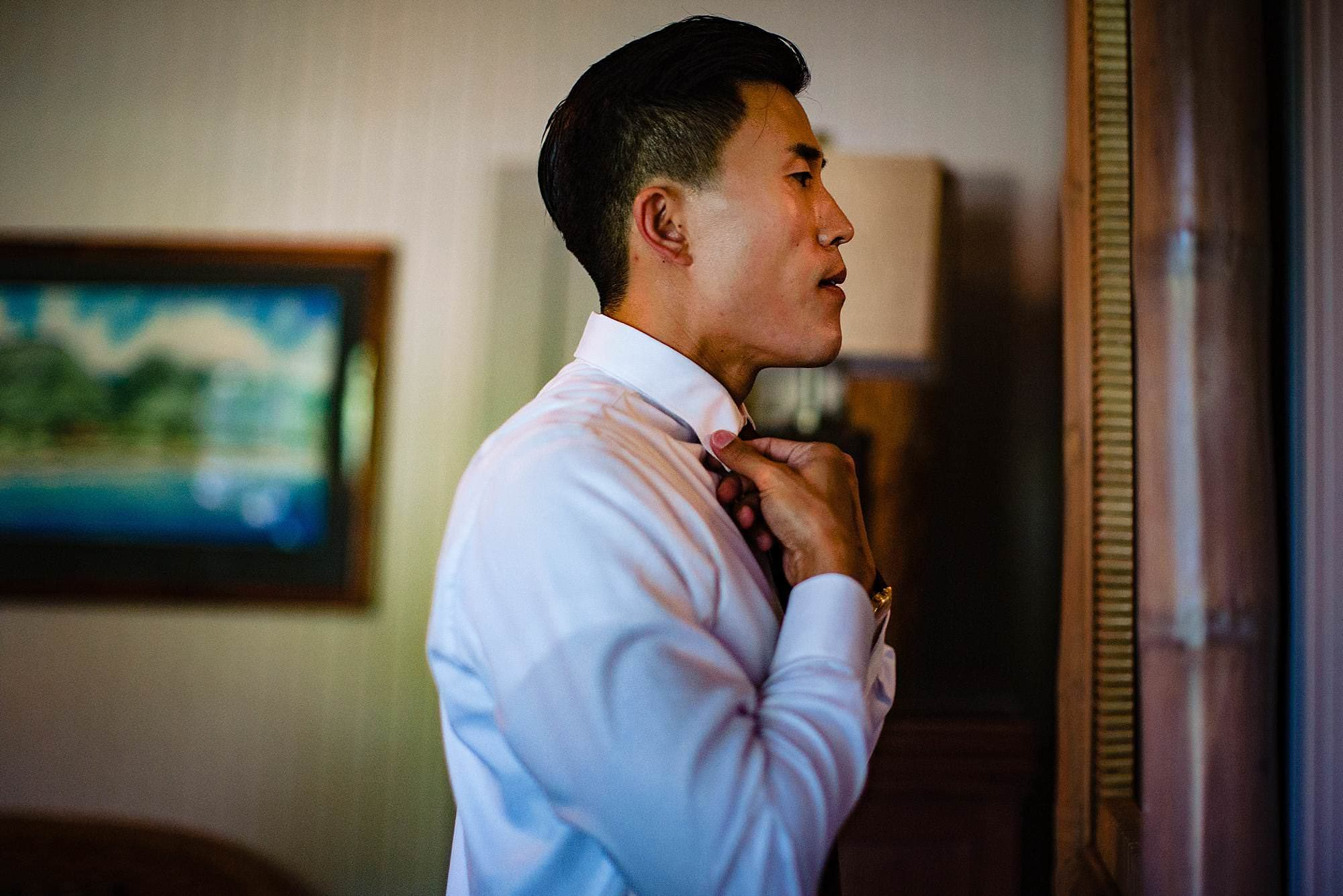 groom straightening his tie at Olowalu Plantation House